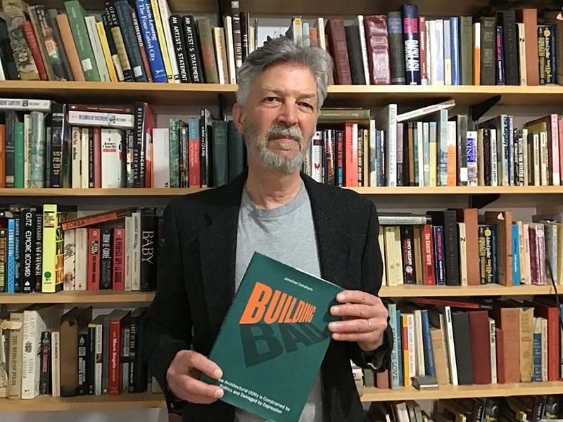 Author Jonathan Ochshorn with copy of his book, Building Bad